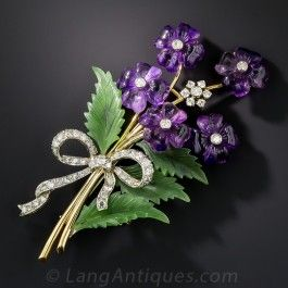A cheerful and charming bouquet composed of purple amethyst diamond centered petals, a single all-diamond flower, and hand carved nephrite jade leaves, is nicely tied-up in a glittering diamond bow in this colorful, festive and sizable (3 by 1 1/2 inch) brooch, hand-fabricated in two-tone 18K gold, of mid-twentieth century vintage. Very likely of Austrian origin.