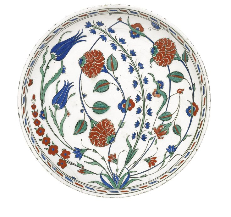 An Iznik polychrome pottery dish with hyacinths, tulips and roses, Turkey, circa 1575 - of rounded rimless form, decorated in underglaze cobalt blue, green and relief red with black outlines, with roses, tulips, hyacinths and prunus stems emanating from a leafy tuft, border with geometric design, exterior with stylised motifs, drill hole to edge for hanging 30cm. diam.