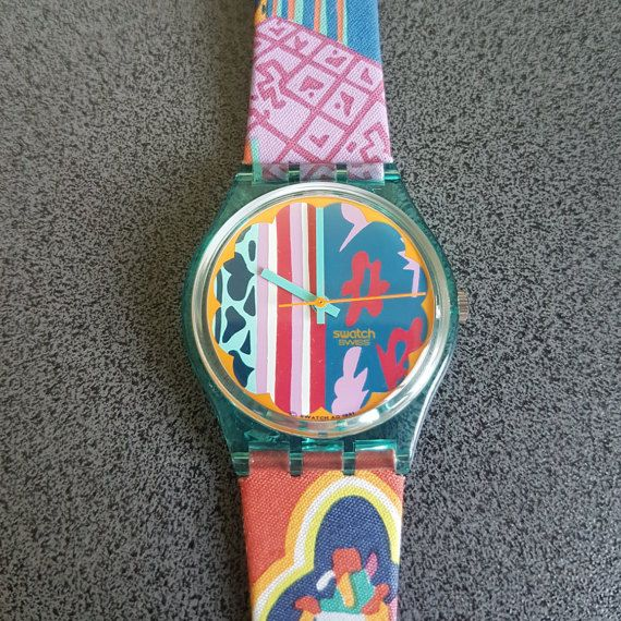 """1992 Vintage Swatch Watch Mogador GL103, Floral Swatch Model, Perfect for a gift    1992 Vintage Swatch Watch Mogador GL103  Water resistant 30 meter / 100 Feet.  Diameter case 33 mm.  New, never worn    Up for bid is a new 1992 Collection Swatch """"Mogador"""" GL103. Comes with new battery installed, original case and pamphlet. Watch has never been worn and is in perfect working order. Measures: Case 34 mm, strap width 17 mm, length 38 mm. Strap is textile over leather.Payment: PayPal only."""