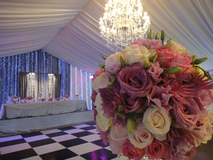 Such beautiful shades of pink flowers and exquisite lighting and draping in the backround