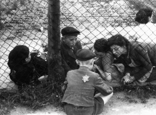 Una familia judía dice adiós a un niño a través de una cerca de alambre en el guhetto de Lodz en Polonia antes de ser deportado a Chelmno. Lodz, Polonia, Septiembre de 1942. Fotografía de Mendel Grossman (fotógrafo internado en Lodz).