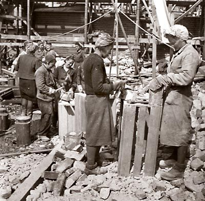Finnish women helped the war effort in many ways.  In this photograph they are cleaning the brick for re-use in construction after the bombing of Jyväskylä.