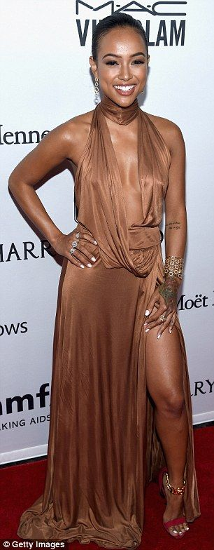 Skin is in:Karrueche Tran sizzled in a plunging bronze dress, slashed at the thigh to show off her toned legs