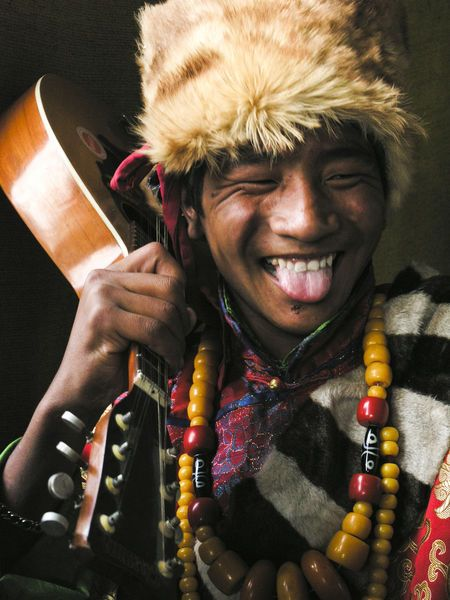 Smile ..... A young tibetan in traditional costume hold a guitar | © Chris Christidis