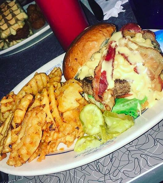 Mac & Cheese Burger - Beef patty with lettuce, tomato, pickle, topped with mac & cheese and bacon all served in a potato bun with waffle fries on the side!    This beauty was created and demolished @ Ellen's Stardust Diner NYC #Burger