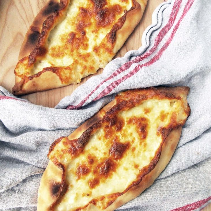 Cheese Pide Recipe Breads with all-purpose flour, luke warm water, instant yeast, olive oil, salt, sugar, mozzarella cheese, feta cheese, eggs