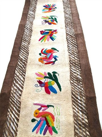 This Otomi embroidered animal wall hanging is made with paper from the bark of the Jonote tree. It's soaked in a hot water bath with natural dyes such as flowers, ash, etc. Later the pulp strips are placed on a board in a grid form and hammered with a flat stone until the paper holds its form. Often the paper is decorated with natural found objects such as seeds and molded into fantastic patterns nothing short of amazing. These pieces have embroidered fabrics like on the Mexican coverlets…