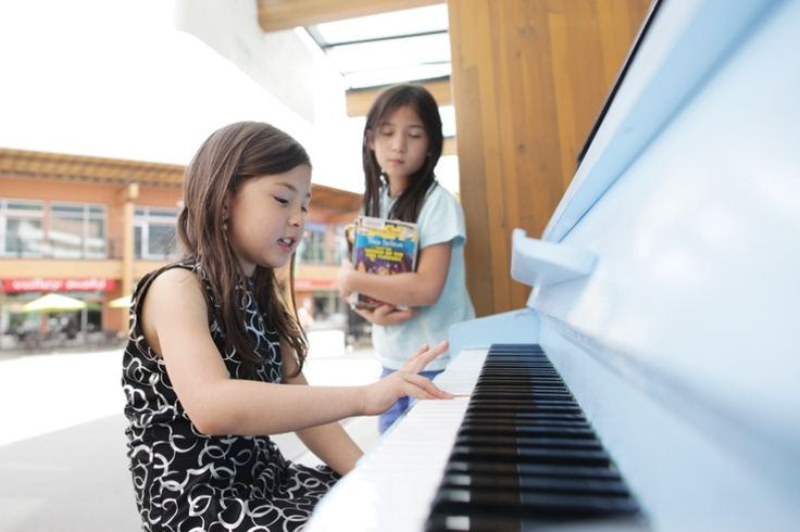 Kaelyn Stark, 7, looks on as Siena Bruno, 6, plays a tune on the new outdoor piano at Lynn Valley Village. photo Lisa King