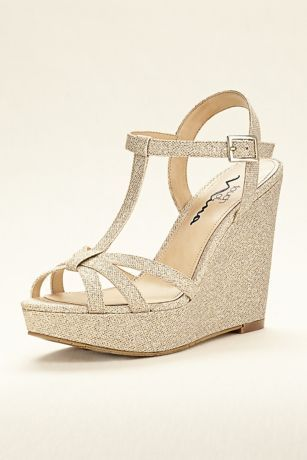 """Glitter fabric adds just the right amount of shine and glitz to this high heel t-strap wedge sandal!  T-strap wedge sandal features ankle strap and buckle.  Heel height: 4.5"""" with 1"""" platform.  Fully lined.  Synthetic sole.  Imported."""