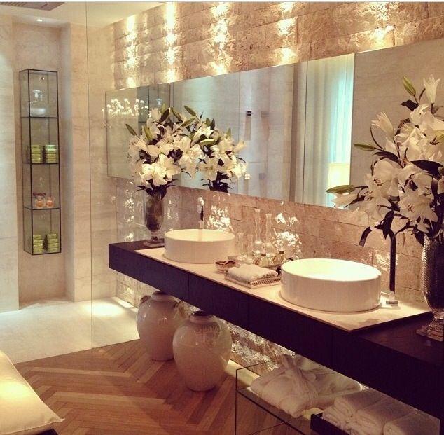 Banho casal com 2 cubas, parede com revestimento aparente e iluminação pontual. Ambiente charmoso.