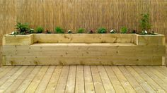 Softwood decking for the garden with a full depth raised flower bed and bench made with large 3 x 9 inch pressure treated purlin type timber incorporating a bamboo covered frame for a backdrop.