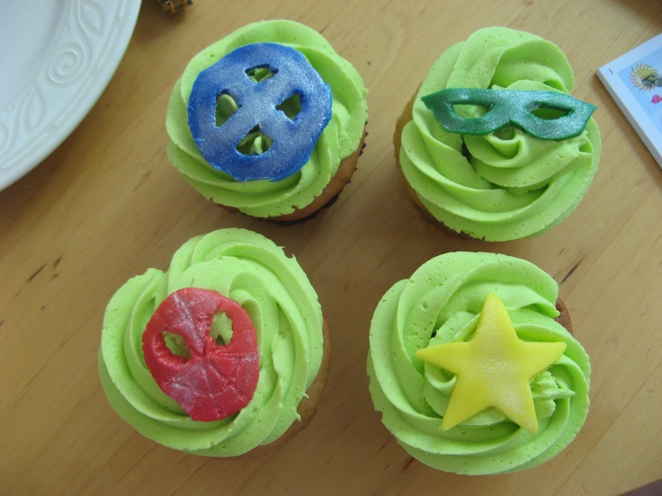 Simple superhero motif cupcakes    Hand-cut fondant stars, Spiderman mask, Green Lantern mask, X-Men symbol. Brushed with silver luster dust. Green tinted raspberry faux IMBC frosting, peanut butter and jelly cupcakes.
