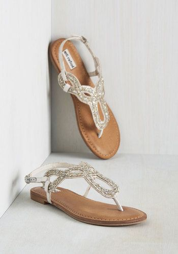 As you sashay the streets in the early morning light, these white sandals catch the eye of passersby with their gleaming embellishments! Aglitter with beads and faceted faux gems, these shimmering flats show there's no difference between your spirit and their effervescence!