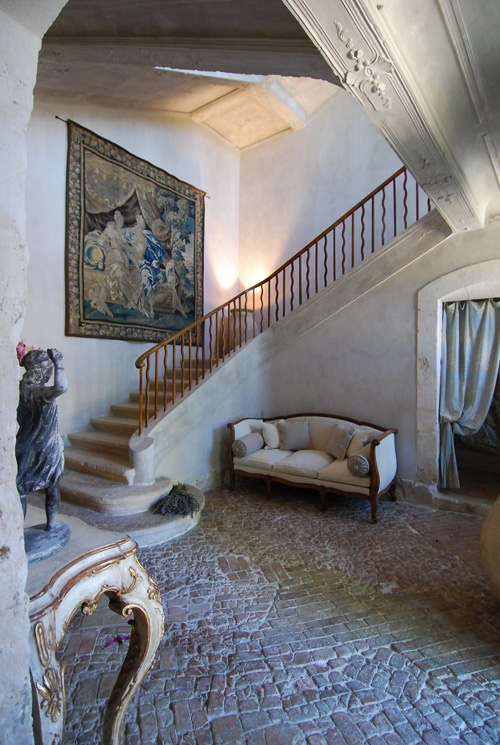 Tapestry. Chalky walls. Sweeping staircase. Towering ceilings. Stone & brick floor. Elegant aged furnishings. France.