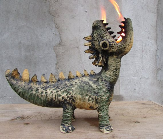 This sculpture of a fire breathing dragon measures 25 cm / 9.8 high, 10 cm / 3.9 wide and 30 cm / 11.8 from chin to end of tail. It weighs 1.5 kg / 3.3 lb  His belly is hollow, and torch oil can be put inside. By adjusting the thickness of the wick you can set how big the flame to be.  As a piece of decoration it can be placed anywhere indoors. For lighting purposes its better to use it outdoors because depending on the oil you use, there can be smoke and soot around the flame.  The…