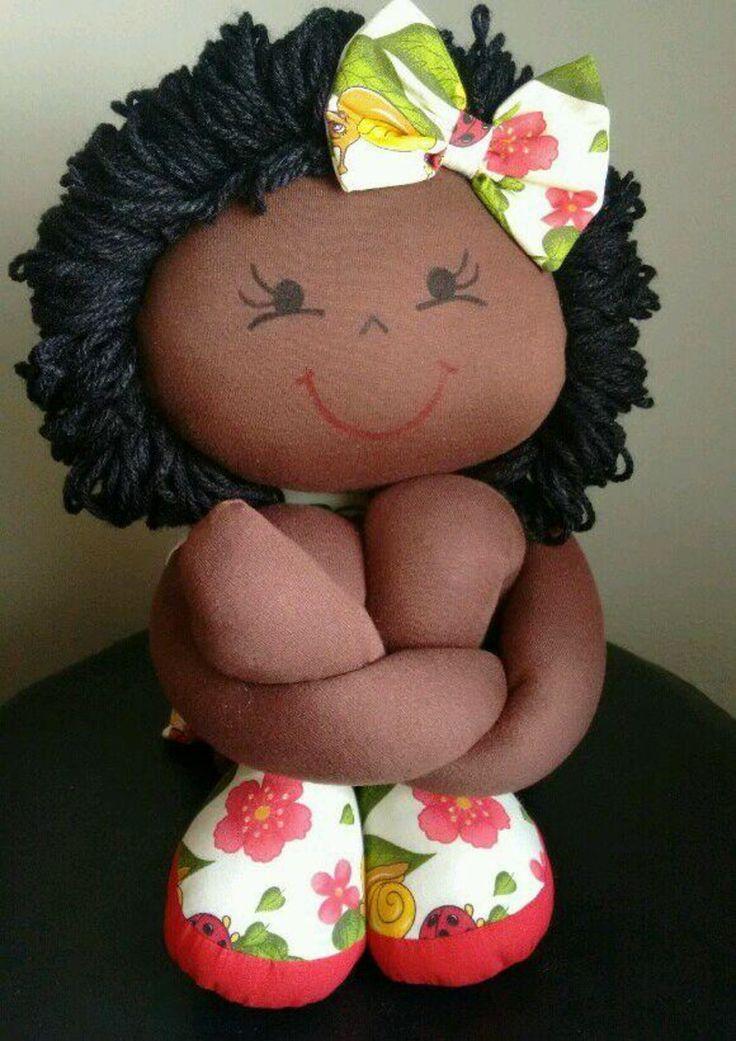 Boneca negra: corpo em malha com enchimento de fibra siliconizada e cabelos em lã. Roupa em tricoline. Posição sentada aproximadamente 30 cm Esticada 60 cm