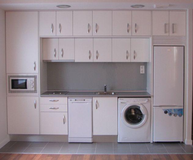 Una cocina completamente amueblada con muebles a medida y equipada con todos los electrodomésticos, con un diseño pensado para conseguir el mayor espacio posible. La cocina está compuesta por: armarios de cocina, refrigerador, microondas, estufa, horno, lavadora, lavavajillas.