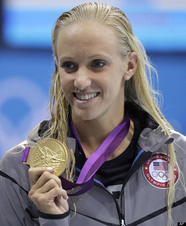 United States' Dana Vollmer holds her gold medal for her win in the women's 100-meter butterfly swimming final at the Aquatics Centre in the Olympic Park during the 2012 Summer Olympics in London, Sunday, July 29, 2012.