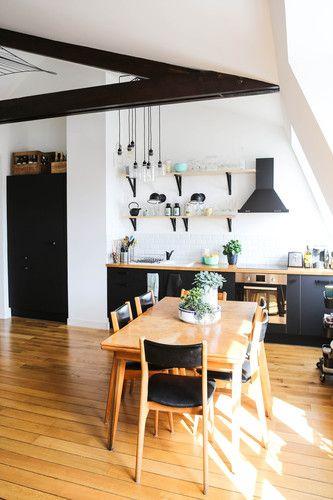 Une cuisine en noir mat avec du mobilier vintage intemporel et plein de caractère