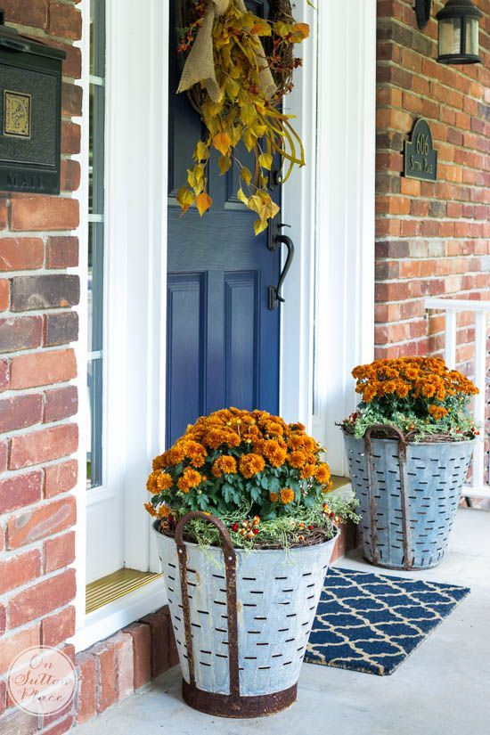 A sophisticated take on the rustic look of galvanized metal, these olive buckets filled with mums decorate Ann of On Sutton Place's front porch. A great example of a fresh spin on an old favorite, in this case, richly-colored fall mums. || @adrake606