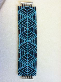"""A wonderful Peyote (Gourd) stitch bracelet in a geometric design using Matte Black and Turquoise colored Miyuki Delica beads. 1 5/8"""" wide and 7"""" long with a 3 ring Sterling Silver tube clasp (5 ring t"""