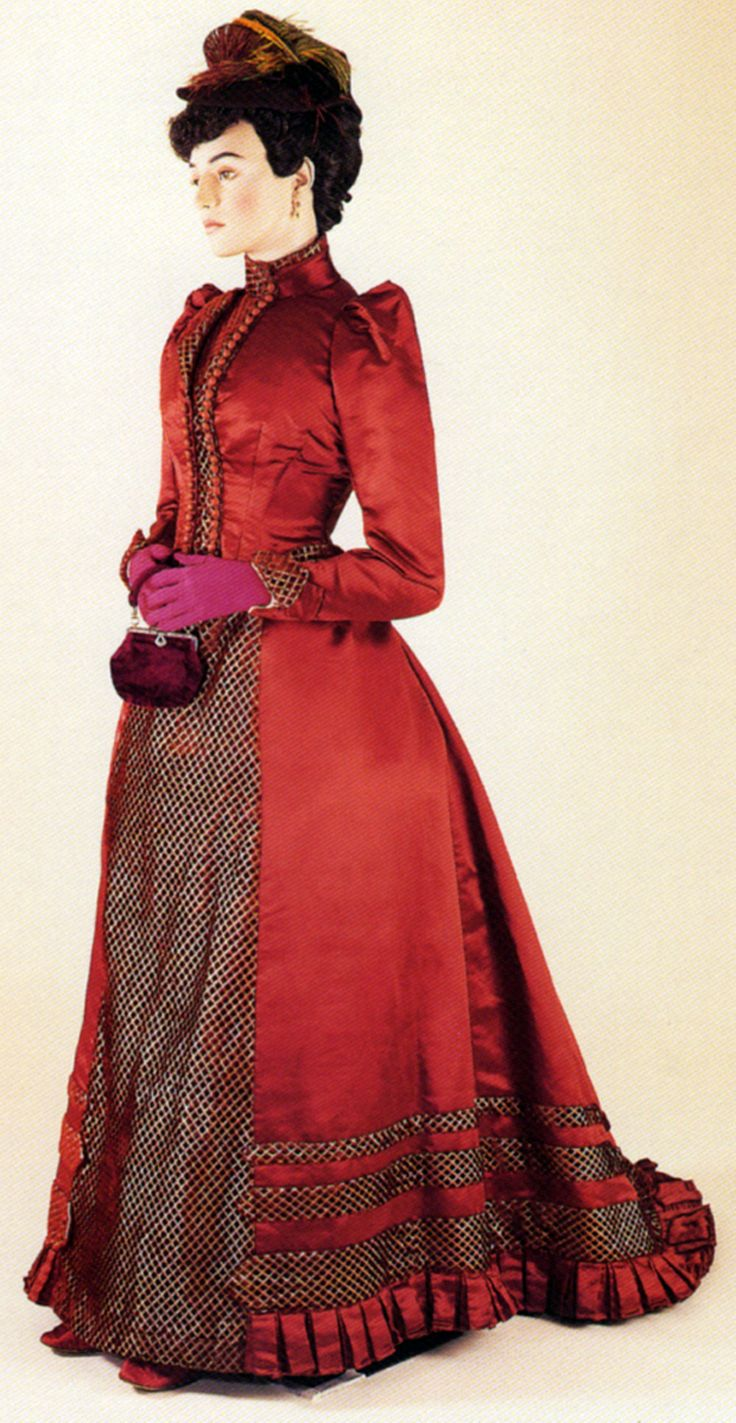 A red silk satin day dress with velvet panels, which would have been worn over a crinolette in order to give the correct fashionable silhouette. Bath Fashion Museum