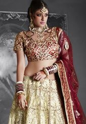 Off white flare net resham, zari, stone and patch embroidered work lehenga. Contrasting red heavily cutwork embroidered choli and net dupatta.  The bust size of the semi stitched choli can be customized upto 40 inches. The waist and hip size of the semi stitched lehenga can be customized upto 40 and 44 inches respectively. The length of the lehenga is 44 inches. Lehenga style can be customized as shown only. The inner of the lehenga is made of brocade fabric. (Slight variation in color and…