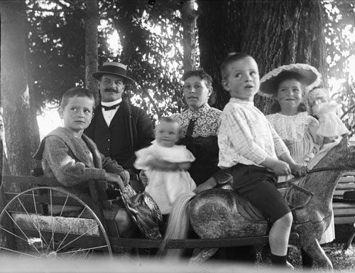 Gruppbild, familjebild. Man och kvinna med fyra barn poserar runt leksakshäst med vagn i park