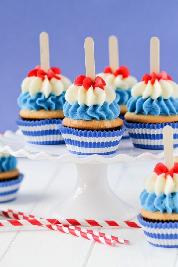 These Bomb Pop Cupcakes recreate the flavor of an ice cream truck fave, the Bomb Pop!  The lemon/lime cupcakes are infused with raspberry and topped with layers of blue raspberry, lime, and cherry butter cream! Click through for recipe!