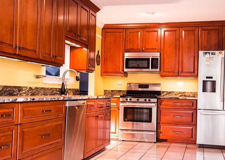 This kitchen had its cabinets refaced with raised panel for Cherry kitchen cabinets with glass doors