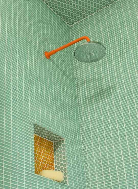 A beautiful mint green and orange shower combines penny tile and with thin rectangular tile bars