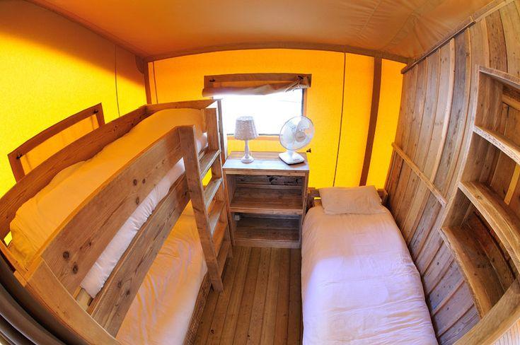 Tente climatisée équipée d'environ 35 m² 2 chambres à coucher / 5 personnes maximum 1 chambre avec 1 grand lit (largeur 160 cm) 1 chambre à 2 lits superposés + 1 lit simple (largeur 80 cm) Coin repas – Cuisine équipée avec frigo top, four micro-ondes, plaques à gaz et vaisselle pour 5 personnes. Salle...