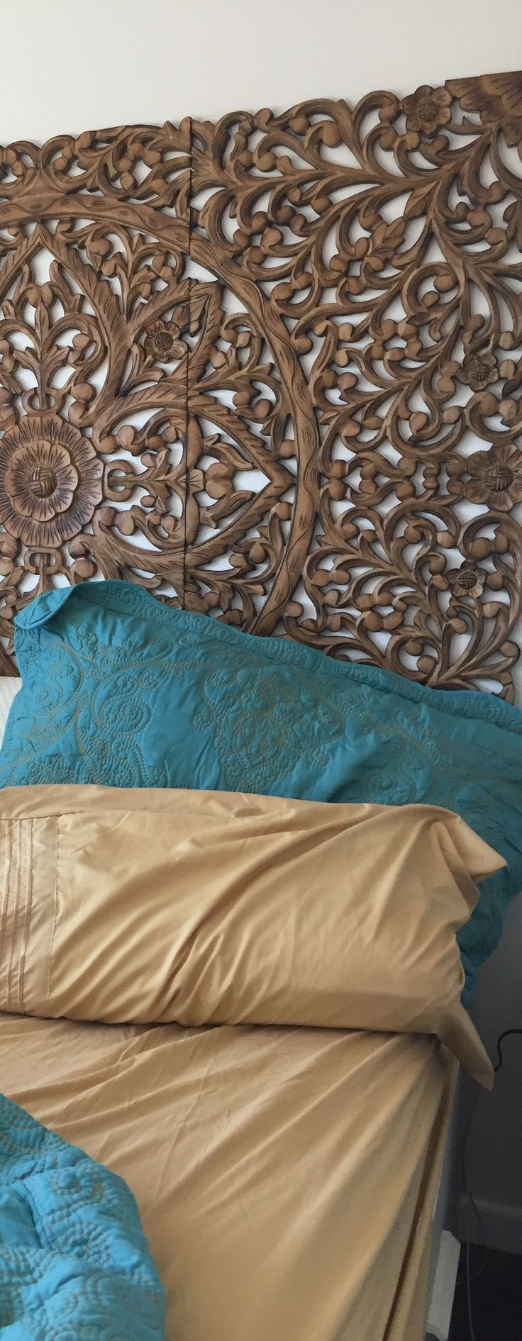 Balinese carved wall art as headboard and quilt teal and gold bedding
