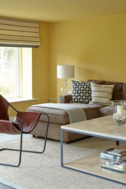 A mustard yellow, Sudbury Yellow by Farrow & Ball, was used in the seating nook to create a cozy area. The color is toned down nicely by more neutral colors in the seating and flooring. Transitional Family Room by Eoin Lyons Interiors