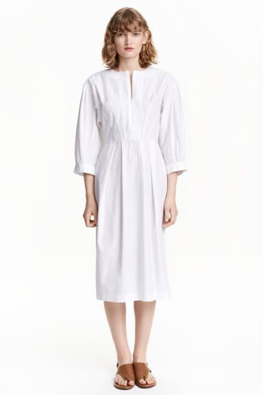 Dress with balloon sleeves: Knee-length dress in a cotton weave with 3/4-length balloon sleeves, a concealed zip at the front and visible zip at the back. Seam at the waist and flared skirt with a pleat front and back. Unlined.