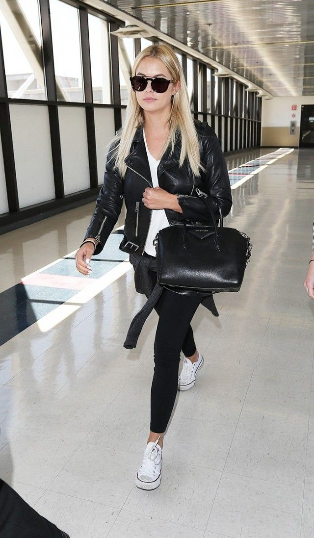 Ashley Benson wears a white t-shirt, moto jacket, skinny jeans, aviator sunglasses, white sneakers, and a duffle bag