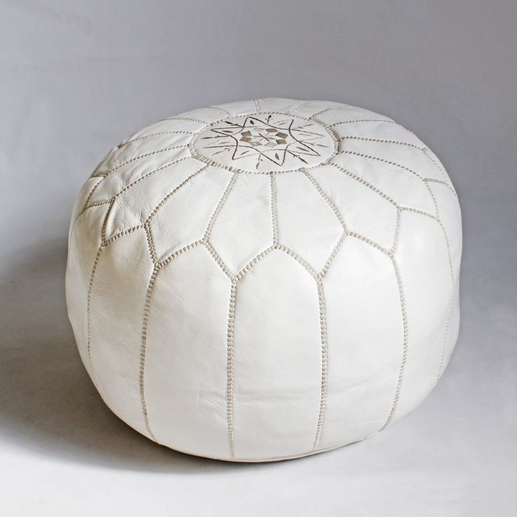 White leather poof stool with beige embroidered stitching.