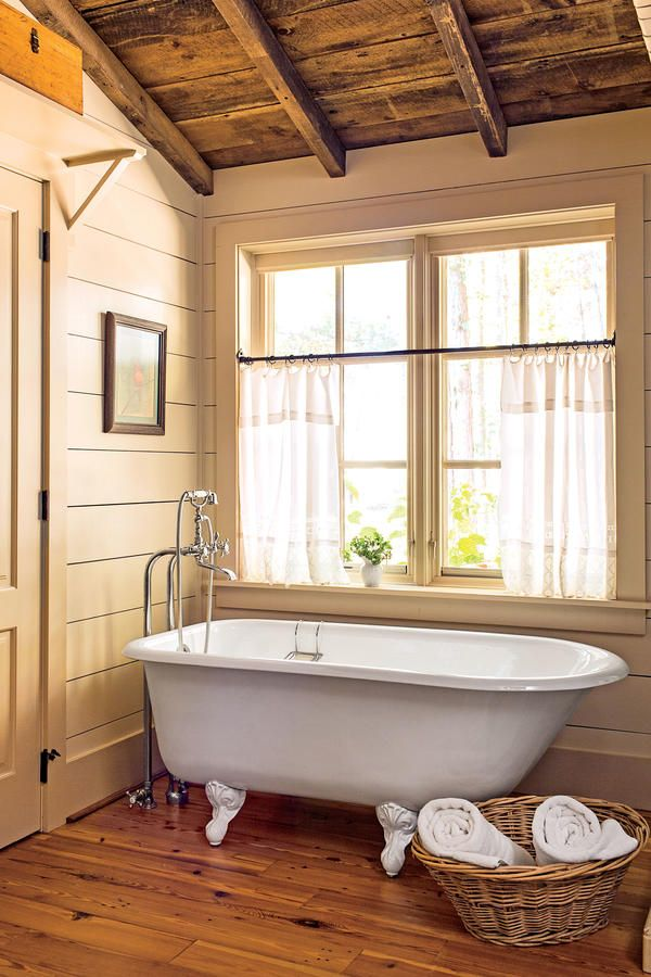 Natural Log Cabin - Stand-Alone Bathtubs That We Know You've Been Dreaming About  - Southernliving. An exposed wood ceiling, stunning wood floors, and a neutral palette create cozy-cabin vibes. The cast-iron claw-foot tub seems to be the perfect place to soak.