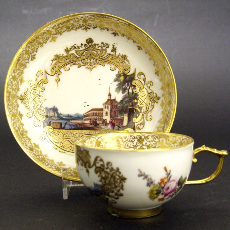 A Fine 18th Century Meissen Porcelain Teacup and Saucer. The Detailed Central Scene Depicts a View of Venice, the Cup is of a Walled Town. A Large Building to the Right Faces the Water which has a Gondola. the Elaborate Gilt Borders are of Laub-und Bandelwerk. The Cup and Saucer is Further Decorated with Deutsche Blumen (German Flowers). The Bases with a Crossed Swords Mark in Under-Glaze Blue for the Meissen Factory. Provenance : From a Private Collection of 18th Century European Porcelain.