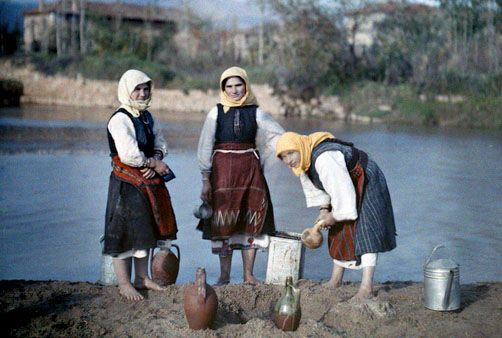 Women filter water taken from riverside pools to use for drinking, near Jugoslavian Frontier