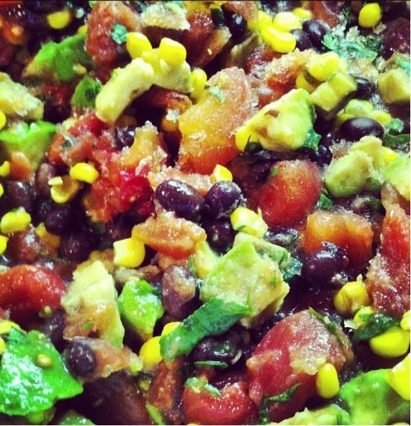 A colorful salsa with avocado, black beans, corn, tomatoes, red onions, and lime juice
