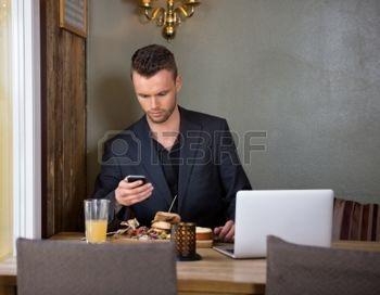 man%3A+Zakenman+Messaging+Op+Mobilephone+terwijl+Gelet+Maaltijd+in+Cafe