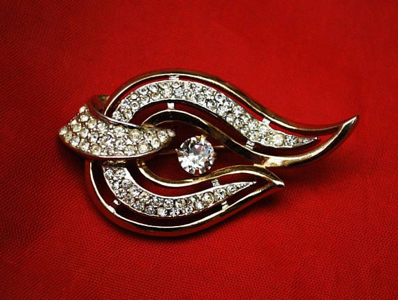 for your consideration is this mid-century Rhinestone Brooch by Kramer. Kramer was founded by Louis Kramer in 1943 and is known for excellent quality rhinestone jewelry. this piece does not have copyright symbol so date this piece before 1955. the brooch consist of clear