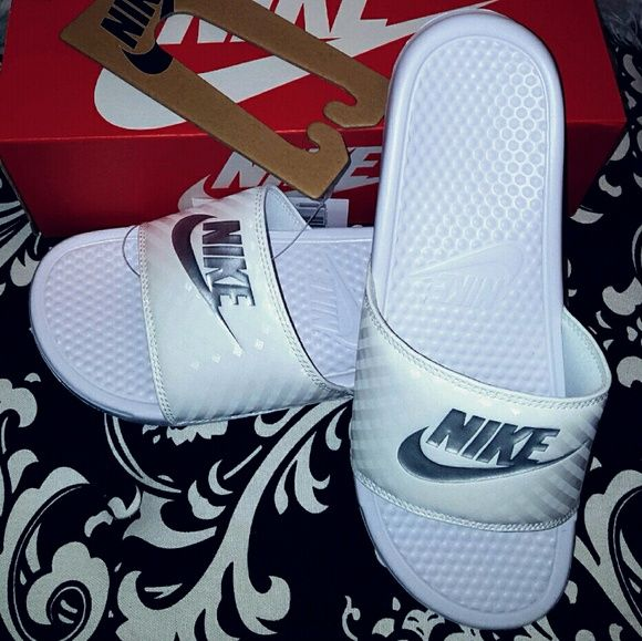 NIB NIKE BENASSI Slides Slip On Flip Sandals-10 This is a pair of new in the box Nike Benassi white slip-on sandals. Great for casual looks and slipping on in an instant! White with silver. Women's size 10. Open to reasonable offers. Just remember these are new in the box Nikes so I might not have as much wiggle room as I would like! More sizes in my closet! Nike Shoes Sandals