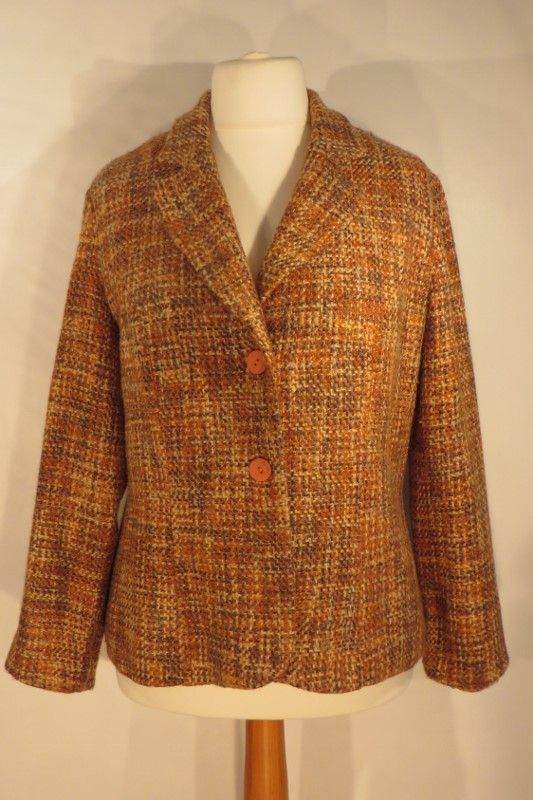 Vintage brown/orange boucle jacket, 16.   Lovely brown, orange and buttermilk 100% wool boucle jacket. The buttons are an unusual 'grained' peach style. The body is lined.   Size: 16 Measurements: B: 44, W: 40, H: 45, L: 25, S-S: 18 Label: None Decade: est.1970 Material: Wool  Cleaning instructions: Dry clean