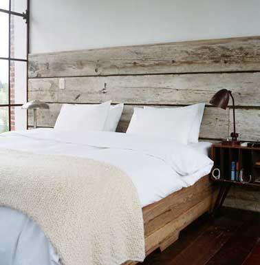 Ambiance naturelle pour la déco de cette chambre grâce à une tête de lit réalisée avec des planches de bois flotté. Nettoyées et poncées, les planches sont fixées en quatre points sur le mur. Une tête de lit qui s'harmonise parfaitement le sommier du lit en bois et le style rétro des lampes et du chevet.