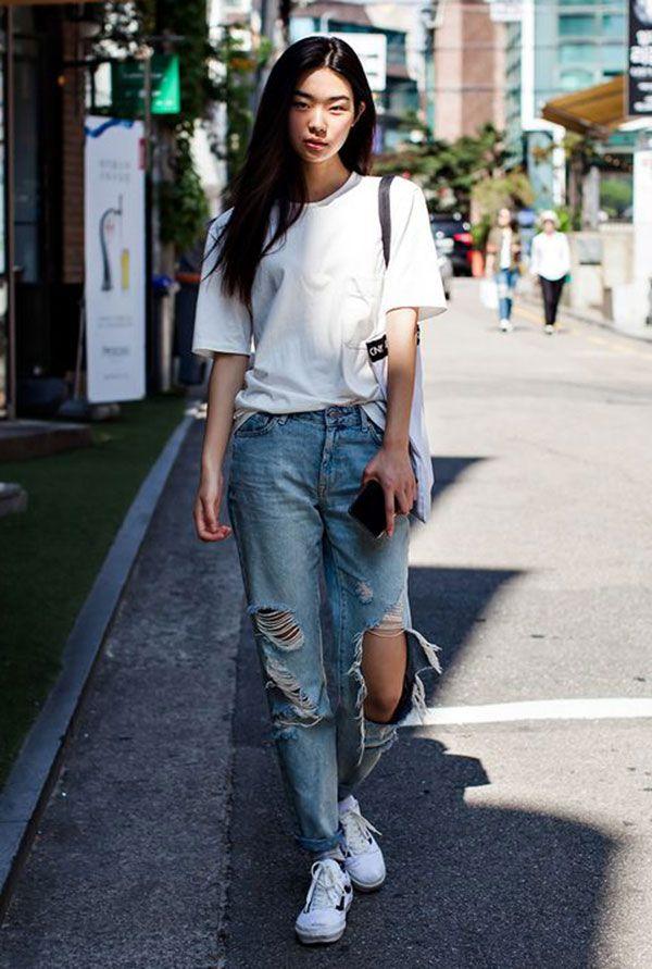 Street style look com camiseta branca, calça destroyed e tênis.