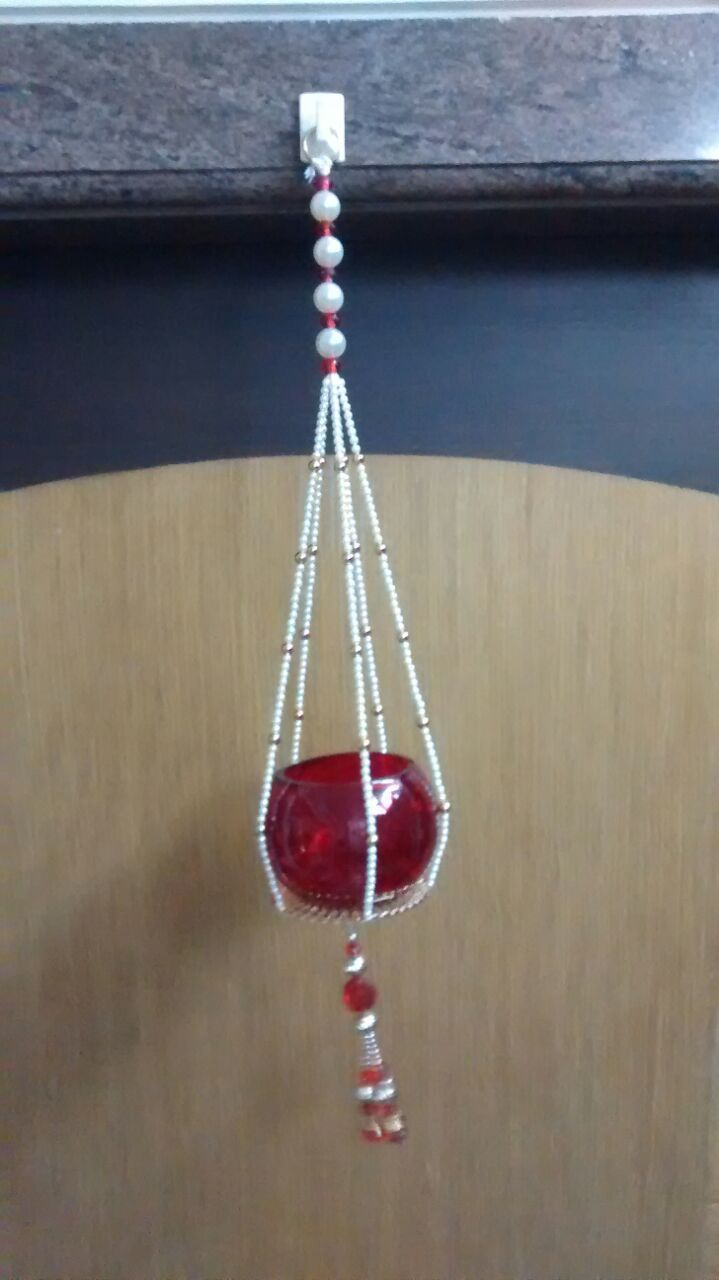"""Beautiful red acrylic candle holder hanging in between strings of white pearls, red and gold beads with red tassels at end. Length : 18"""" each.  To inquire more or place an order, call or whatsapp us on +91 99 200 66 996."""