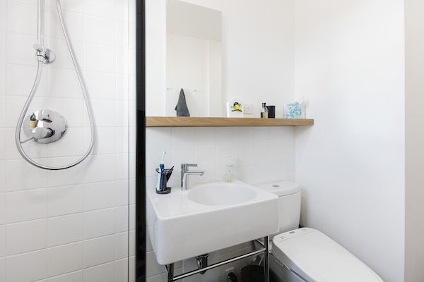 We utilized a minimalist material palette for the bathroom: honed slate tile floors and white subway tiles for the walls, with a floating white oak shelf above the sink for a touch of warmth.