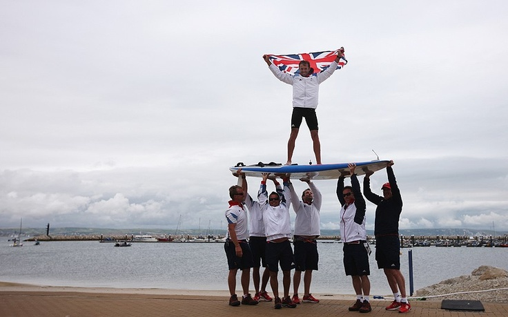 Nick Dempsey of Great Britain is carried onshore on his windsurf board by Team GB team mates after winning the silver medal in the RS:X Men's Sailing on Day 11 of the London 2012 Olympic Games